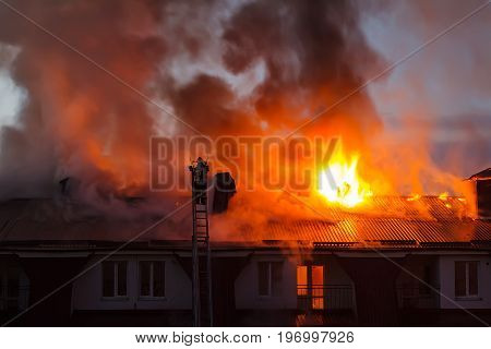 Burning fire flame with smoke on the apartment house roof in the city firefighter or fireman on the ladder extinguishes fire.