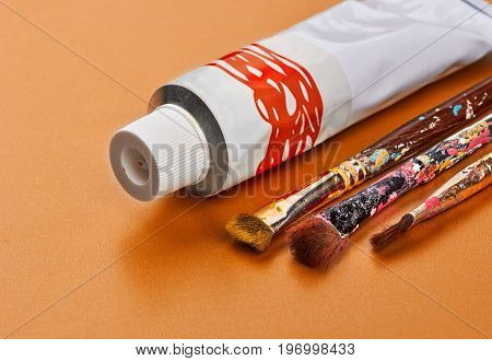 Vintage Artists Brushes With Yube Paint On An Orange Background.closeup.copy Space