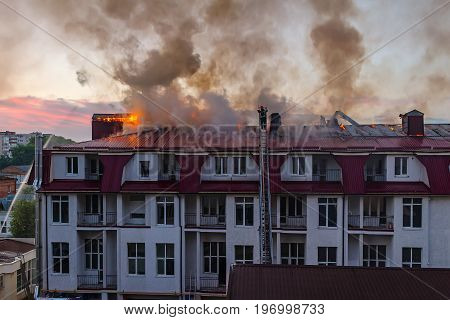 Burning fire flame with smoke on the apartment house roof in the city firefighter on the ladder extinguishes fire.