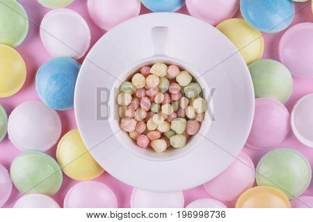 Small pastel color sweeties in a white cup on pink table.