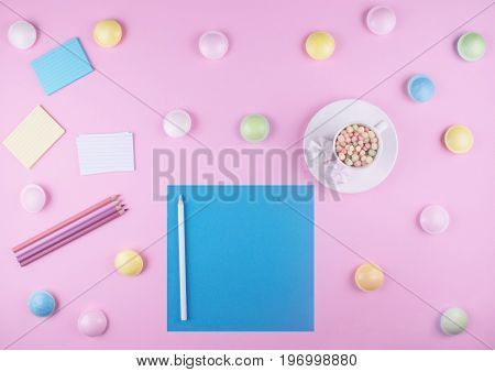 Table desk with set of colorful supplies, cup, sweets, colored paper on pink background. Top view and copy space for text. Work and education concept.