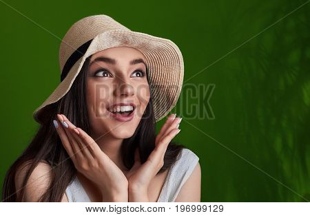 Portrait Of Surprised A Smiling Pretty Girl In Summer Hat Posing Isolated Over Green Tropic Backgrou