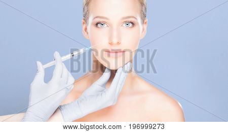 Young and beautiful woman having skin injections over blue background. Plastic surgery concept.