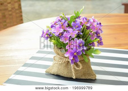 Purple flowers in small jute bag on the table - soft focus