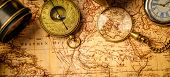 Old vintage retro compass and spyglass on ancient world map. Vintage still life. Travel geography navigation concept background. Top view. poster