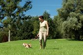 Senior woman walking her dog in a park poster