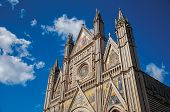 Facade details of the opulent and monumental Orvieto Cathedral (Duomo) under sunny blue sky in Orvieto, a pleasant and well preserved medieval town. Located in Umbria, central Italy poster