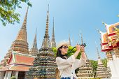 Chinese woman tourist photographer taking pictures with dslr of the wat pho temple Bangkok Thailand. asian girl visiting and looking around the sightseeing building architecture. poster
