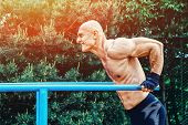 Man doing push ups on parallel bars in a park poster