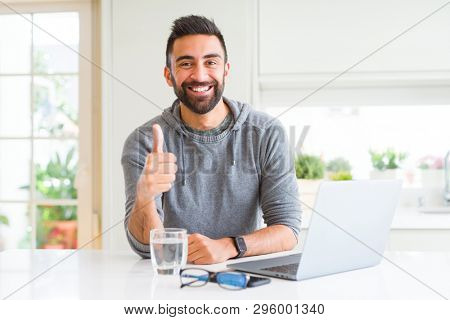 Handsome hispanic man working using computer laptop doing happy thumbs up gesture with hand. Approving expression looking at the camera with showing success.