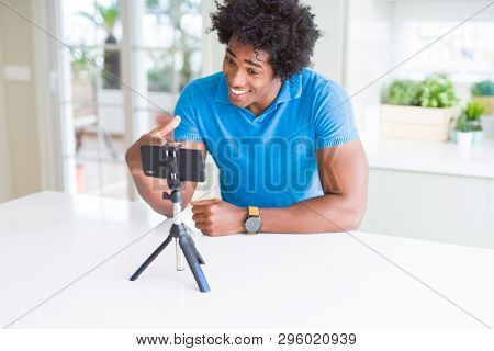African American man doing online call with webcam using smartphone very happy pointing with hand and finger poster