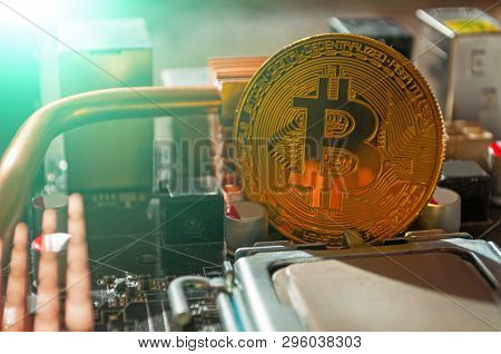 Golden bitcoin among the electronic computer elements. Business concept of digital cryptocurrency. Blockchain technology, bitcoin mining business concept