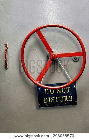 Do Not Disturb Warning Sign Plate Hanging On A Hermetic Bomb Shelter Armored Door