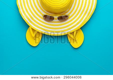 poster of top view of yellow sunglasses, striped summer retro hat and flip-flops. summer concept on the turquoise blue background. flat lay minimalist shot of yellow summer beach accessories. photo of yellow summer accessories with copy space