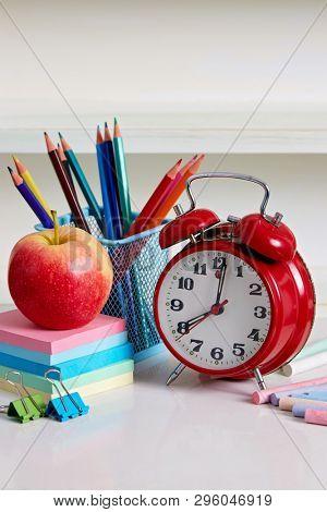 School supplies. Alarm clock with apple and school supplies. Back to school conceptual image.