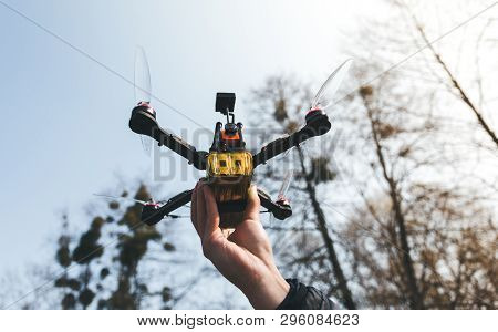 Pilot racing drone holds in his hand fpv copter before launching it. A small high-speed aircraft with a remote control in the hands of an experienced racer poster