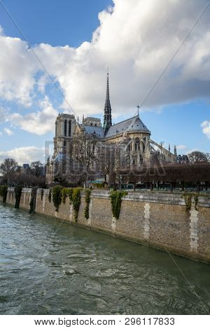 Notre Dame Cathedral in Paris. Springtime view. of the rear elevation with spire and rear flying buttresses, taken from across the river Seine.