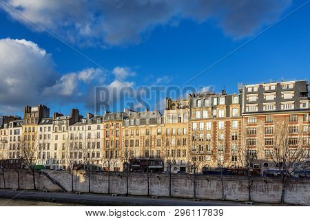 Classis architecture of Paris, France. A row of townhouses along the banks of the River Seine during golden hour. Early eveing sunlight.