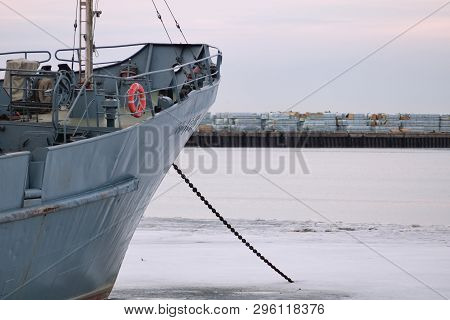 Standing On The Prow Of A Ship Anchored In The Bay In Winter