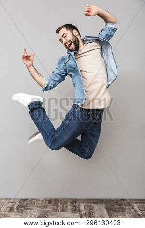 Full length portrait of a happy young man wearing shirt jumping over gray background, celebrating