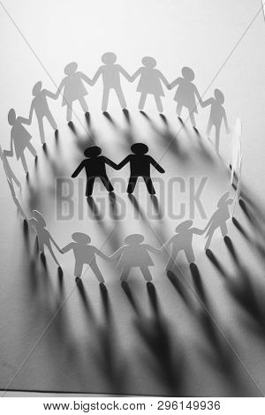 Paper figure of male couple surrounded by circle of paper people holding hands on white surface. Minorities, bulling, diversity concept.