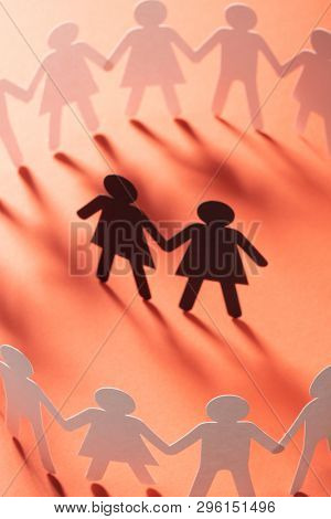 Paper figure of female couple surrounded by circle of paper people holding hands on red surface. Minorities, bulling, diversity concept.