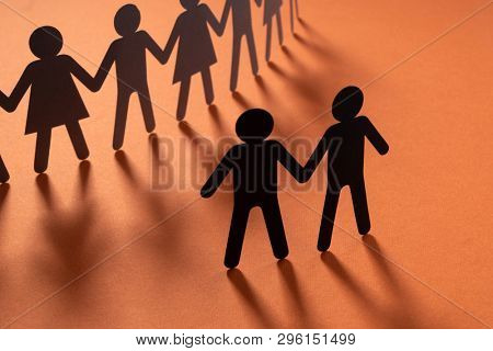 Black paper figure of male couple in front of a crowd of paper people holding hands on redsurface. Social movement, protest, minorities concept.