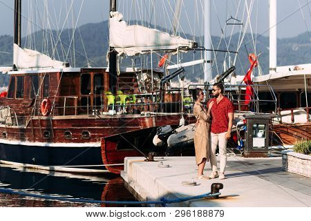 Man And Woman Near The Yachts On The Dock. Couple In Love At The Yacht. Couple In Love On The Dock.
