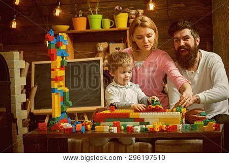 Playroom Concept. Little Child Play With Toy Bricks In Playroom. Son With Mother And Father Build St