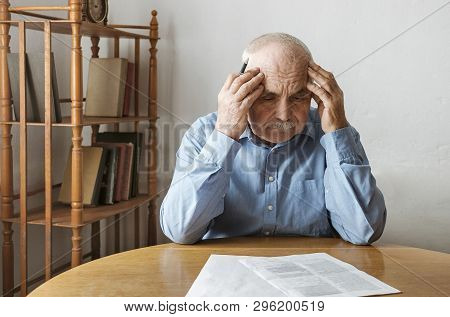 Depressed, Concerned Senior Man Doing Paperwork Sitting At A Table With His Head In His Hands Starin