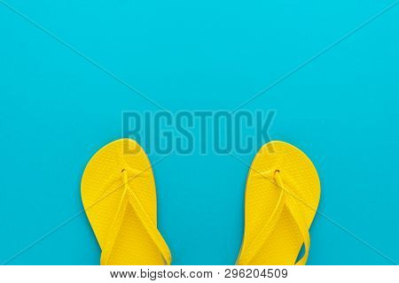 Pair Of Yellow Beach Flip-flops On The Blue Background Summer Concept. Minimalist Flat Lay Photo Of