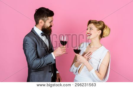Woman In White Dress And Handsome Man In Suit Dating In Restaurant. Couple Holds Glass Of Red Wine.