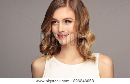 Blonde Woman With Curly Beautiful Hair Smiling On Gray Background. The Girl With A Pleasant Smile.