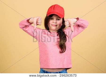 Being Thumbs Down. Little Kid Expressing Disapproval For Clothing And Accessory. Adorable Girl Showi