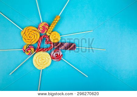 Many Colorful Lollipop Candys Arranged In Heap With Heart Shaped Candy In The Center On Blue  Backgr