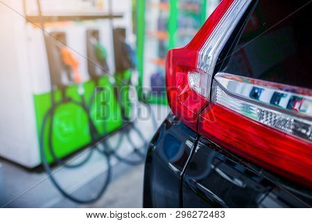 Selective Focus To The Car With Blurry Refilling The Car And Fuel At The Gas  Station Background