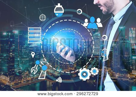 Young businessman looking at smartphone over night city background with double exposure of GUI with internet icons. Concept of hi tech in business poster