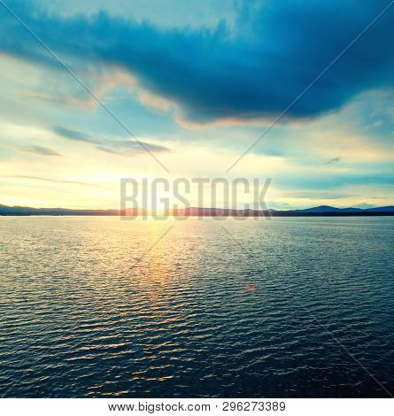 Sea sunset landscape. Sea water surface lit by sunset light. Summer sunny sea water scene in vintage picturesque tones. Sea summer nature with mountains at the horizon - panoramic sea view