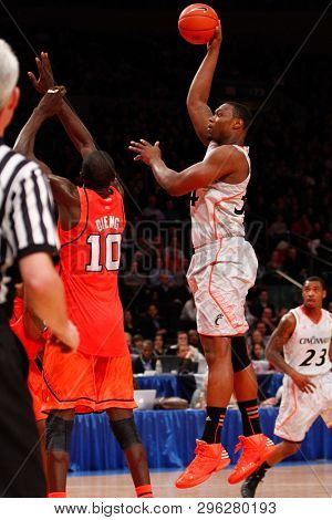 NEW YORK-MAR 10: Cincinnati Bearcats forward Yancy Gates (34) shoots over Louisville Cardinals center Gorgui Dieng (10) during the Big East Tournament on March 10, 2012 at Madison Square Garden.