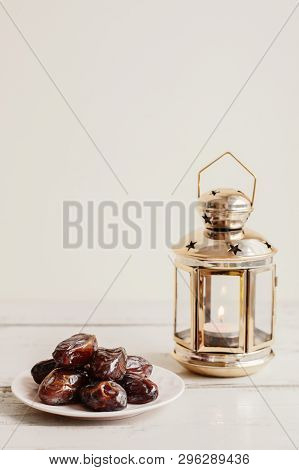 Dried Dates And Gold Colored Lantern With Burning Candle On Wooden Table. Traditional Sweet Food Dur