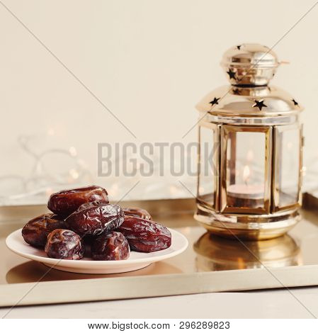 One Portion Of Dried Dates And Gold Colored Lantern With Burning Candle On Metal Tray. Ramadan Karee