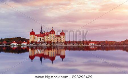 Splendid Morning Scene. Moritzburg Castle Near Dresden With Colorful Sky During Of Sunrise, Reflecta