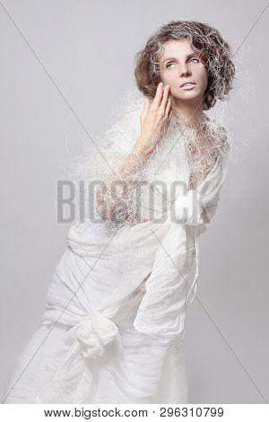 Model Girl In A Fantasy, Fairy-tale Image Posing In A Fashionable Cotton Haute Couture Dress On A Wh