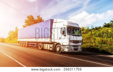 Big White Truck On The Road In A Rural Landscape At Sunlight. Perfect Sky. Over The Aspfalt Road At