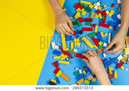 Vilnius, Lithuania - February 23, 2019. Children Hands Play With Colorful Lego Blocks On The Table
