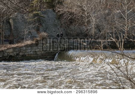 Cumberland, Rhode Island, Usa - February 15, 2008: Man Contemplating The Turbulent Water Flowing Dow