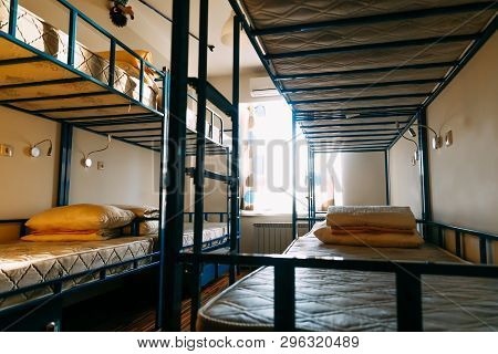 Backpackers Stay In Hotel With Modern Double-decker Beds Inside The Dorm Room For Twelve People. Dor