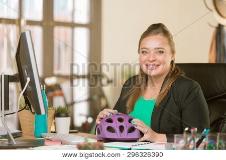 Young Creative Professional Woman At Her Desk With A Bicycle Helmet