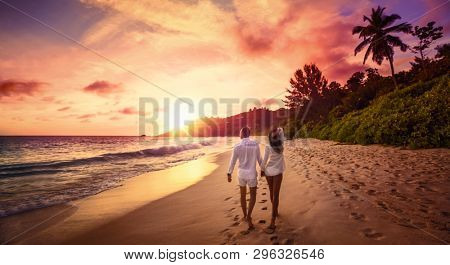 Young Happy Lovers on Beach. Couple Walking on Romantic Travel Honeymoon Vacation Summe Holidays Romance Sunset