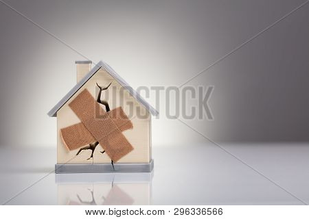 Broken House Model With Crossed Band Aid On Desk